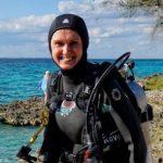 Uśmiechnięta kobieta w stroju nurka idzie do morza w Zatoce Świń