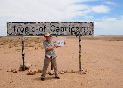 Namibia, Turysta pozuje do fotografii na Zwrotniku Koziorożca, Tropic of Capricorn, GoTravel